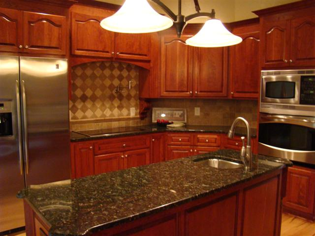 A Beautiful Slab of Granite Tops Rich Maple Cabinetry with an Intricate Tile Backsplash set off by Under Cabinet Lighting